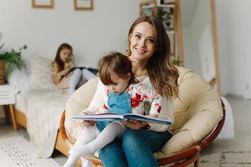 Portrait of a smiling young cute mother and two daughters reading a book relax in the sofa in a bright big white room