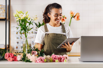 Smiling florist woman holding a digital tablet while standing at the counter in her shop
