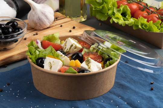 Greek salad in eco packaging with an open lid on blue textile in the interior