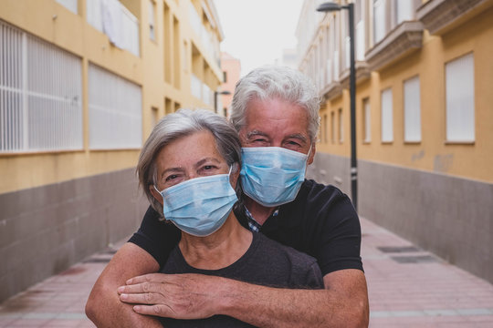 couple of two seniors wearing medical mask to prevent coronavirus (covid-19) or another type of virus - close up of faces in middle of street -  protect people satying safe together - italian people