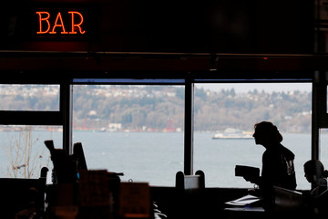 A server works in the dining room of the Athenian Seafood Restaurant in Seattle