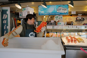 A vendor arranges a display of seafood at the Public Market, amid the coronavirus outbreak,  in Seattle
