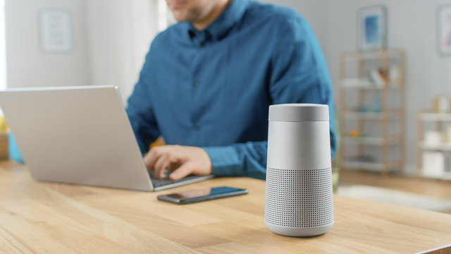 Close Up Shot of a Modern Silver Bluetooth Speaker Standing on a Table at Home. Man in the Background Sits at the Table and Works on His Laptop. Smartphone Lies on a Table Next to Him.