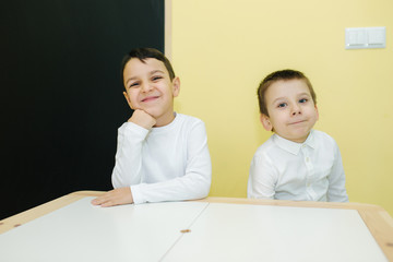 Boys are sitting at the table in kindergarden. Two boys friends