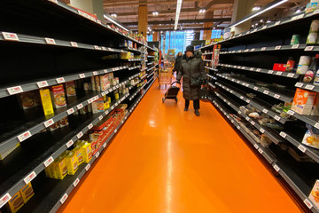 A shopper walks through an aisle empty of pasta, rice, beans and soup at a Loblaws supermarket in Toronto