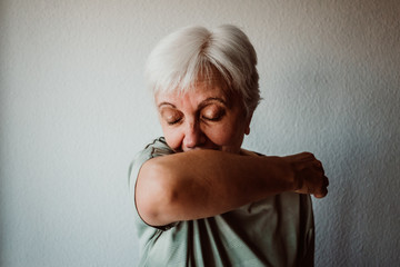 .White-haired, middle-aged woman with coronavirus symptoms coughing correctly on her elbow. Global health crisis. Pandemia