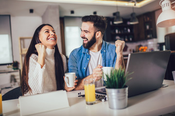 Obraz Happy couple doing business together working at home on the laptop. - fototapety do salonu