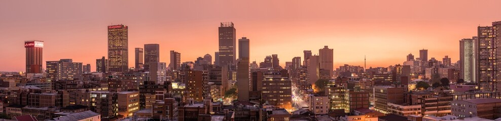 A beautiful and dramatic panoramic photograph of the Johannesburg city skyline, taken on a golden evening after sunset. Fototapete