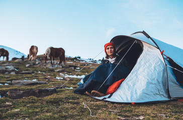 Tuinposter Kamperen girl relax in campsite, tourist in camp tent on mountain nature, hiker woman enjoys wild horses on valley camping trip