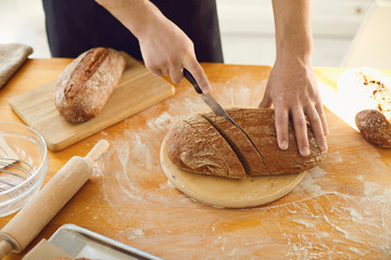 Photo Blinds Bread Hands cutting fresh homemade bread on a table in a bakery kitchen.