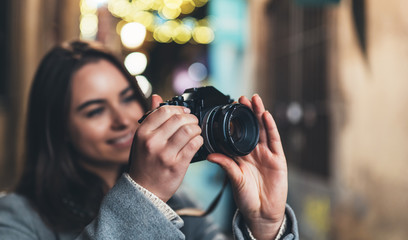 Fotomurales - Photographer girl with retro camera take photo on background bokeh light in night city, Blogger photoshoot concept. Tourist  photo hobby. Outdoor portrait smile woman with video technology.