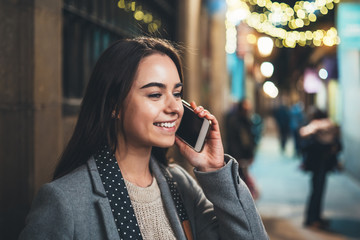 Young smile woman calling mobile phone on background bokeh light in night europe city. Girl  using smartphone technology. Digital business communication, online wi-fi internet