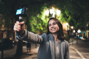 Fotomurales - Female vlogger record with digital camera. Smiling woman taking selfie video on light night city. Traveler making video for her blog. Vlogger uses photo camera for shoot social media