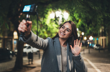 Fotomurales - Female vlogger recording with digital camera showing hi. Smiling woman taking selfie video on light night city. Traveler making video for her blog. Vlogger uses photo camera for shoot social media