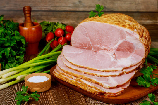 Smoked boneless ham with vegetables and salt on wooden table.