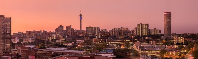 A beautiful and dramatic panoramic photograph of the Johannesburg city skyline, taken on a golden evening after sunset. Fotobehang