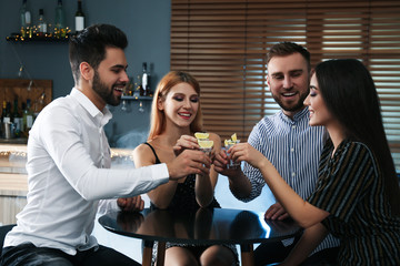 Canvas Prints Bar Young people toasting with Mexican Tequila shots at table in bar