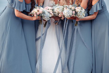 Wall Murals Hydrangea Beautiful blue dridesmaids dresses and bride with fresh hydrangea bouquets