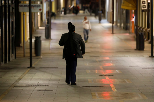 A man walks with his guitar along an unusually almost empty La Bola street as people remain confined inside their homes due to the coronavirus outbreak, in downtown Ronda