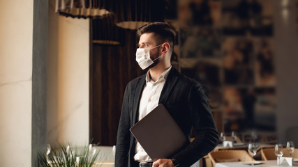 Handsome adult bearded man indoors in cafe. Lifestyle concept photo with copy space. Picture with gray laptop and protective mask on the face