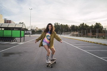 Wide angle shot of a girl on a skateboard in a city