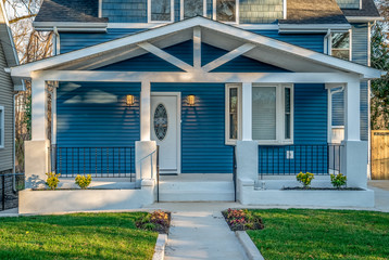 Beautiful renovated craftsman style covered porch with white columns, beams,  black baluster railing in front of a blue horizontal vinyl lap siding single family home in the East Coast USA