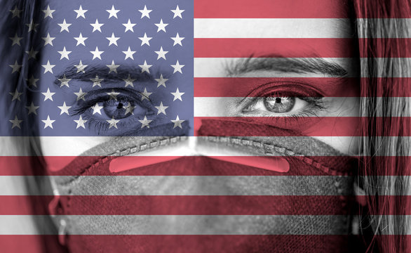 Closeup photo of woman's eyes wearing protective mask against the background of the USA flag.