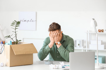 Sad fired man sitting at table in office