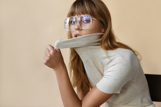 Stylish beautiful fashion girl wear trendy sunglasses looking at camera, retro vogue sexy attractive young model woman blond hair in eyewear posing on beige studio background, portrait