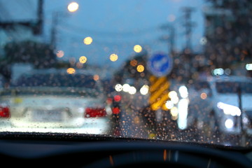Fotomurales - traffic jam on night road city with storm rainy day weather, car driving on street town with water rain drop on windshield outside of bad view