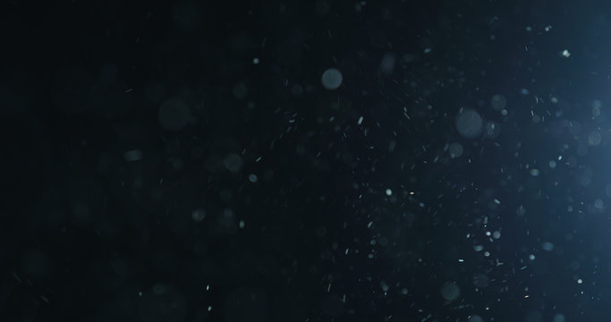 natural dust particles flow in air on black background