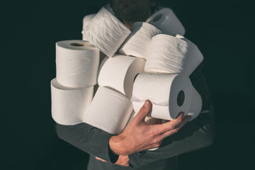 Toilet paper shortage coronavirus panic buying man hoarding carrying many rolls at home in fear of...