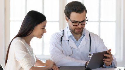 Head shot professional male medical worker wearing uniform showing health check test results on digital tablet to smiling female patient. Pleasant doctor proposing healthcare program to young woman.