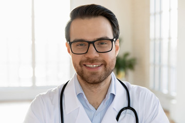 Head shot close up smiling male doctor therapist in eyeglasses looking at camera. Professional...