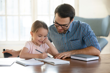 Young father in eyeglasses pleased to see little daughters' study success. Excited smiling small child girl enjoying learning with pleasant dad at home. Children education, home schooling concept.