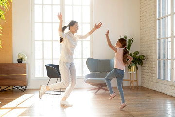 Full length excited young mommy repeating dance moves for school performance with happy small daughter. Joyful little preschool kid girl having fun together with cheerful mother in living room.