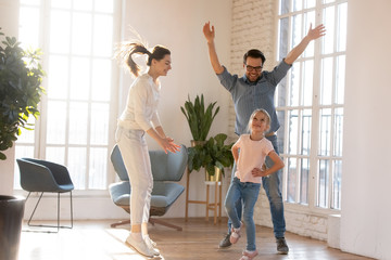 Overjoyed young married couple having fun, watching little preschool daughter dancing in living room. Happy small schoolgirl showing dance moves to excited cheerful supporting parents at home.