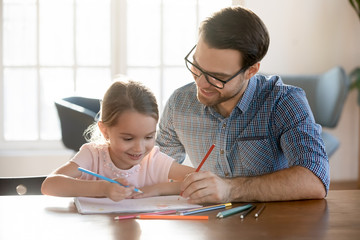 Head shot joyful young dad drawing pictures in paper album with happy small daughter, enjoying free leisure time at home. Smiling little kid girl learning painting with father, sitting at table.