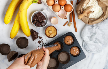 Woman prepares  homemade muffins with banana and chocolate. Ingredients on the table - wheat flour, eggs, brown sugar, chocolate chips, fresh fruit, cinnamon. Selective focus