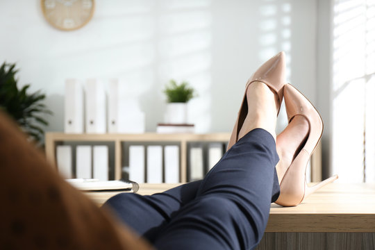 Lazy worker with feet on desk in office, closeup