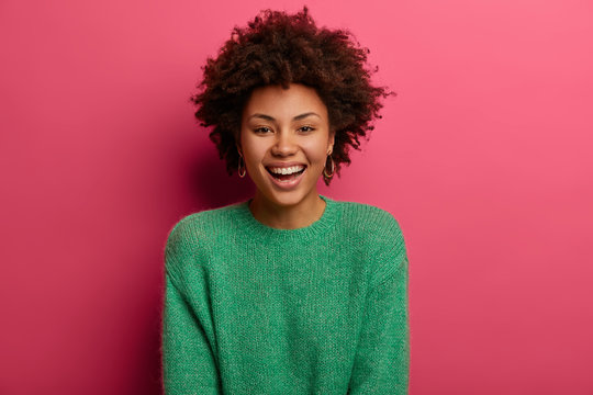Portrait of good looking curly ethnic woman smiles broadly, enjoys day off, has happy talk with interlocutor, discusses holiday preparation, wears green sweater, isolated on pink background.