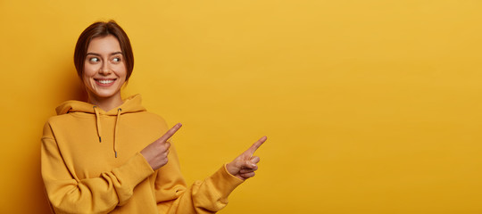Obraz Smiling dark haired woman gives advice and points right, promots product, wears casual sweatshirt, poses against yellow background, indicates at advertisement, introduces promo with pleased expression - fototapety do salonu
