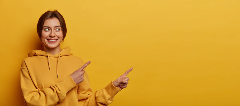 Smiling dark haired woman gives advice and points right, promots product, wears casual sweatshirt, poses against yellow background, indicates at advertisement, introduces promo with pleased expression