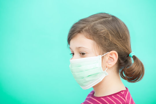 Sad little girl in a green protective disposable medical mask on a green background. Coronavirus Protection Concept, COVID-19. Pandemic 2020