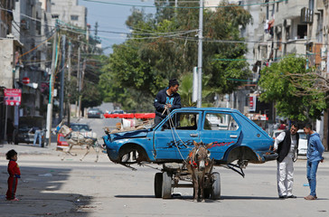A Palestinian man rides a donkey-drawn cart transporting an old car to a scrap yard, in Gaza City