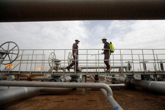 Workers spray disinfectant on pipelines as a preventive measure against coronavirus, at Nahr Bin Umar oil field, north of Basra