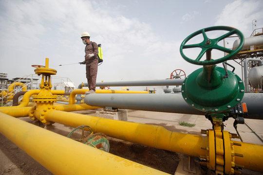 A workerss sprays disinfectant on valves as a preventive measure against coronavirus, at Nahr Bin Umar oil field, north of Basra