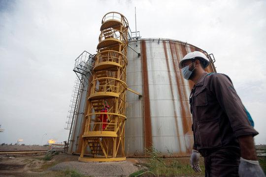 A worker wears a protective mask, following an outbreak of coronavirus, at Nahr Bin Umar oil field, north of Basra