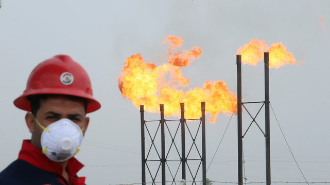 Flames emerge from flare stacks at Nahr Bin Umar oil field, as a worker wears a protective mask, following an outbreak of coronavirus, north of Basra