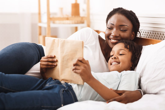 Happy afro family reading book in bedroom